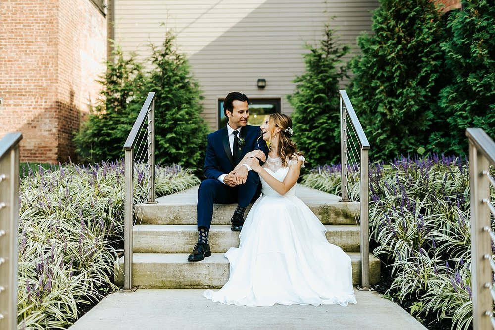 Bride and groom sitting on the steps at the roundhouse