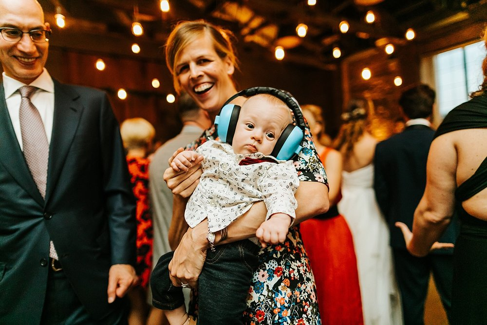 Baby wearing headphones at a wedding reception