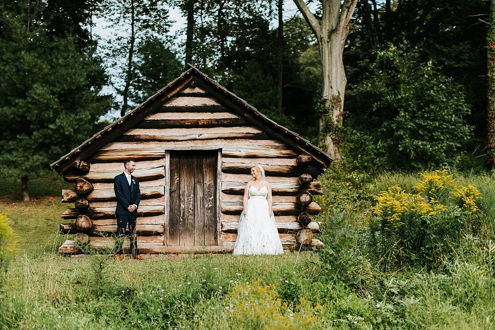 Bride and groom in front of a cabin at valley forge park