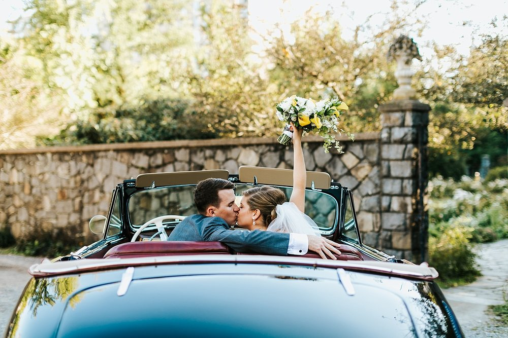 Bride and groom kissing in a fancy car convertible