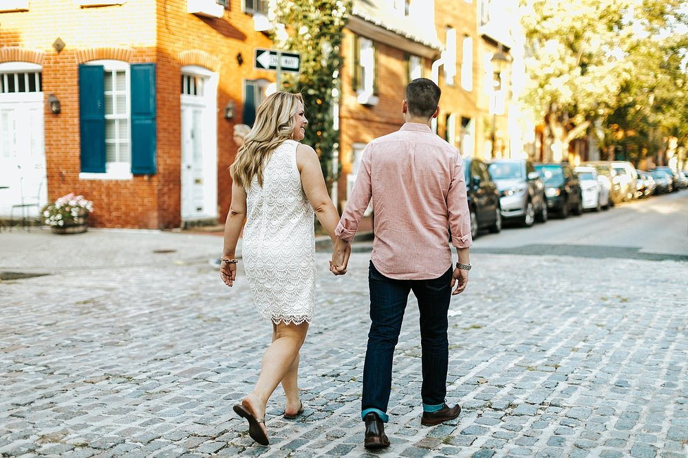 Couple holding hands walking on a cobble stone street at fells point, baltimore