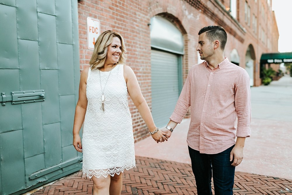 Couple holding hands, walking and looking at each other in fells point