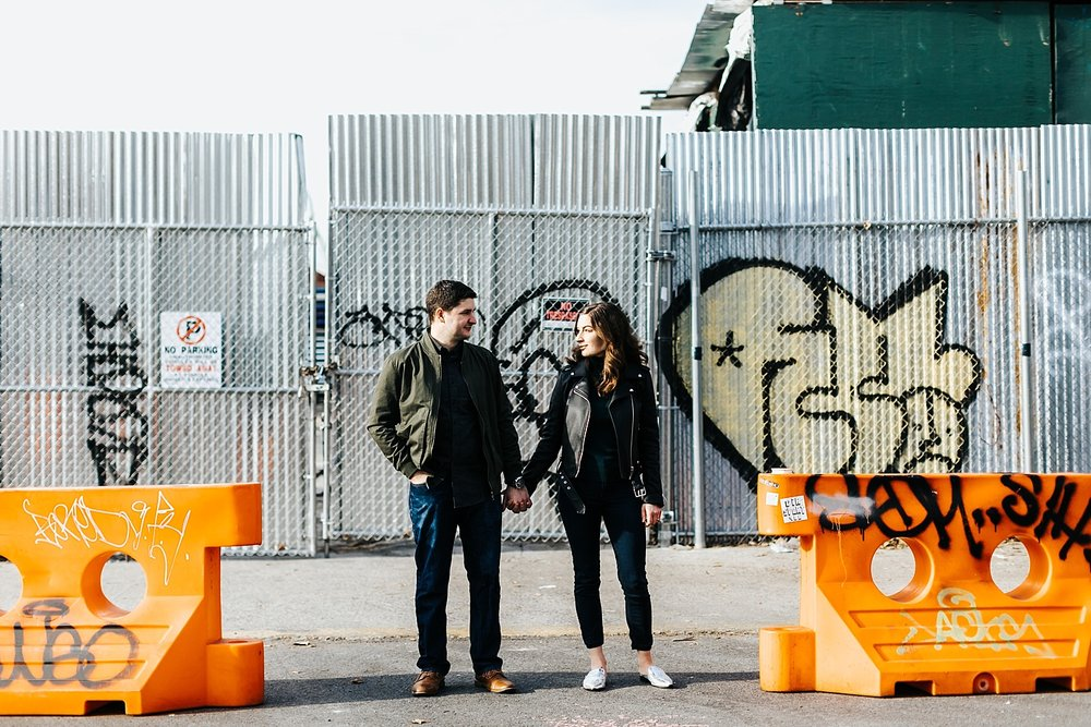 Couple standing outside holding hands surrounded by graffiti at williamsburg, brooklyn