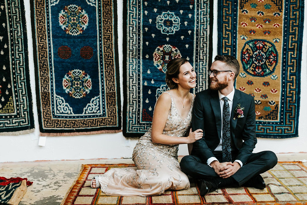Bride and groom sitting on a vintage rug and surrounded by vintage rugs at material culture