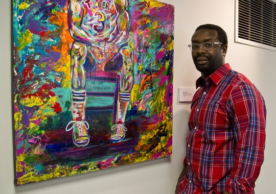 "Boyd Smith stands near work from ""A Colorful Narrative,"" one of the new exhibits at the Art Museum of Greater Lafayette. (Photo: Michael Heinz/Journal & Courier )"