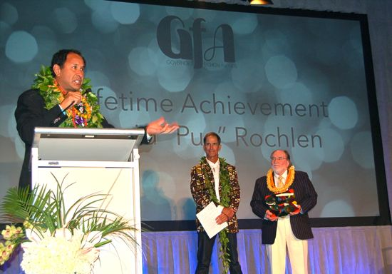 "David ""Pua"" Rochlen of Surf Line Hawaii/Jams World was the winner of the Lifetime Achievement Award at the reinstated Governors Fashion Awards ceremony that took place Oct. 30 at The MODERN Honolulu. Longtime fashion veteran Dale Hope, in a vintage 1965 Sandwich Isles tapa-print jacket presented the award with Gov. Neil Abercrombie. — Nadine Kam photos"