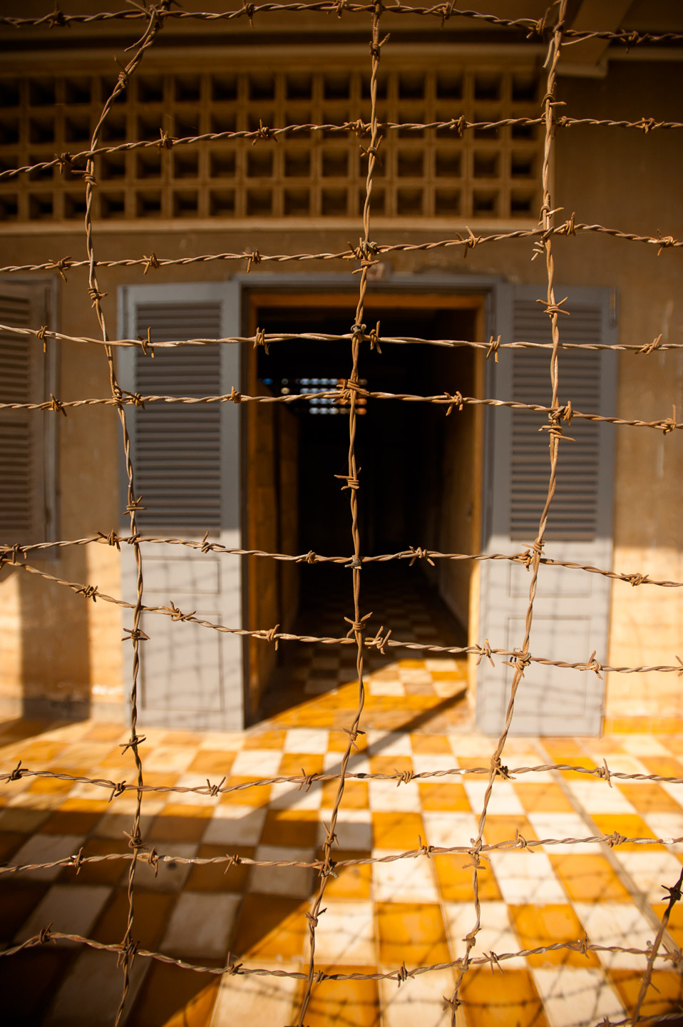 Barbed wire still wraps around some of the buildings used as cell blocks at former S-21 prison, now Tuol Sleng Genocide Museum in Phnom Penh, Cambodia, on December 6, 2013.  Copyright © 2013 Art Zaratsyan