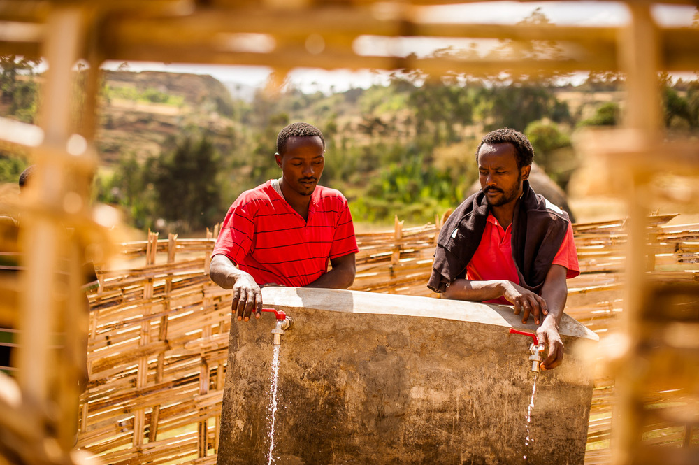 """Good pressure!"" Melkamu, technician and mechanic, and Fetene Demele, land survey specialist from HOPE Ethiopia, test a clean water point in Garbansa Ayche village, a site of a recent large clean water project by HOPE International Development Agency in SNNPR, Ethiopia on January 24, 2014.  Copyright © 2014 Art Zaratsyan"