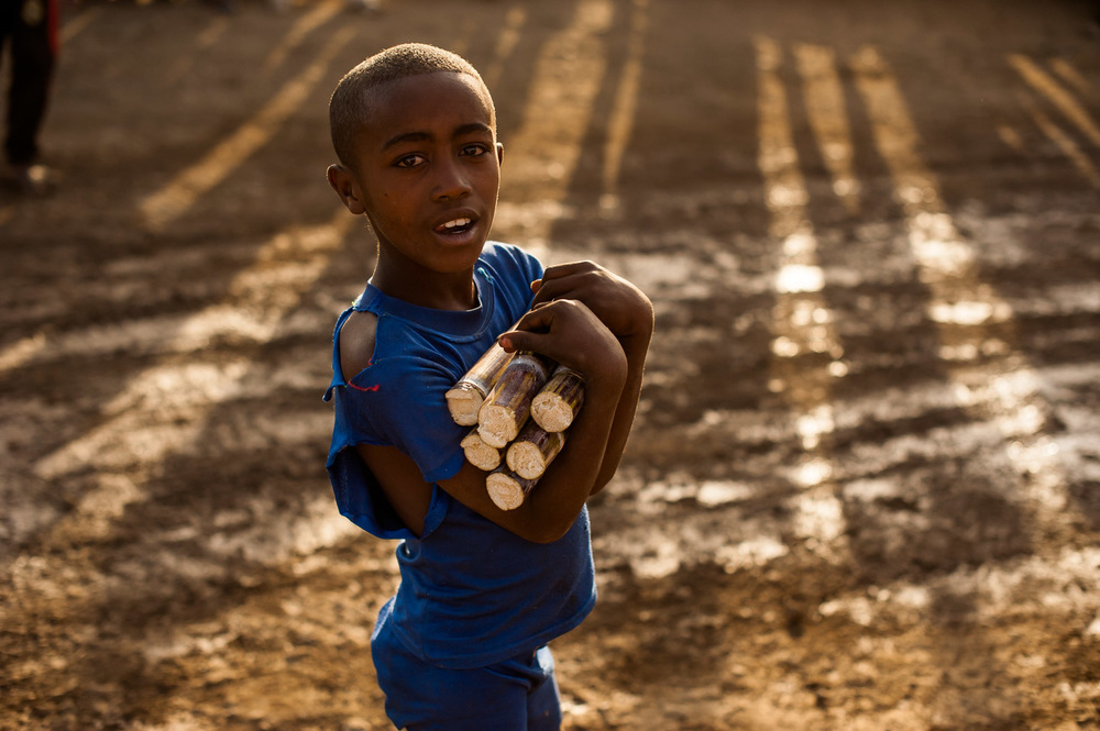 Boy with sugar cane at sunset in the town of Arba Minch, center of operations of HOPE International Development Agency in SNNPR, Ethiopia. January 25, 2014.  Copyright © 2014 Art Zaratsyan