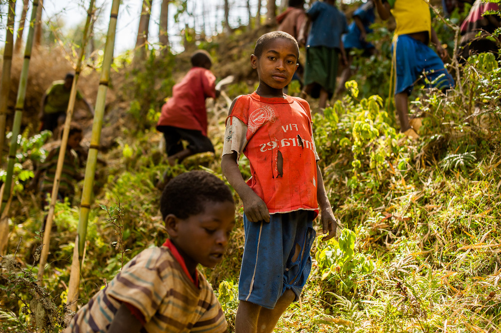A flock of children from Garbansa Ayche village leads me through a bamboo grove to the capped source of a recent large clean water project by HOPE International Development Agency in SNNPR, Ethiopia. January 24, 2014.  Copyright © 2014 Art Zaratsyan