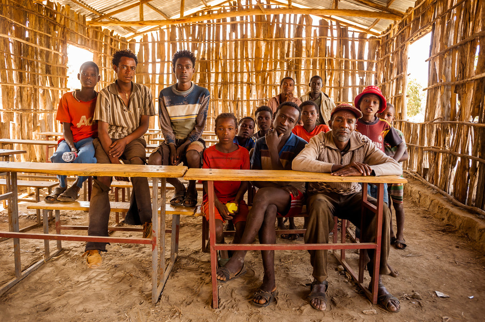 Villagers of Kuera Mukula gather in the local schoolhouse for a group portrait, with only looks of calm curiosity and without any posing. Kuera Mukula is a village in SNNPR, Ethiopia, and a site of an on-going multi-kilometre clean water project by HOPE International Development Agency. January 30, 2014.  Copyright © 2014 Art Zaratsyan