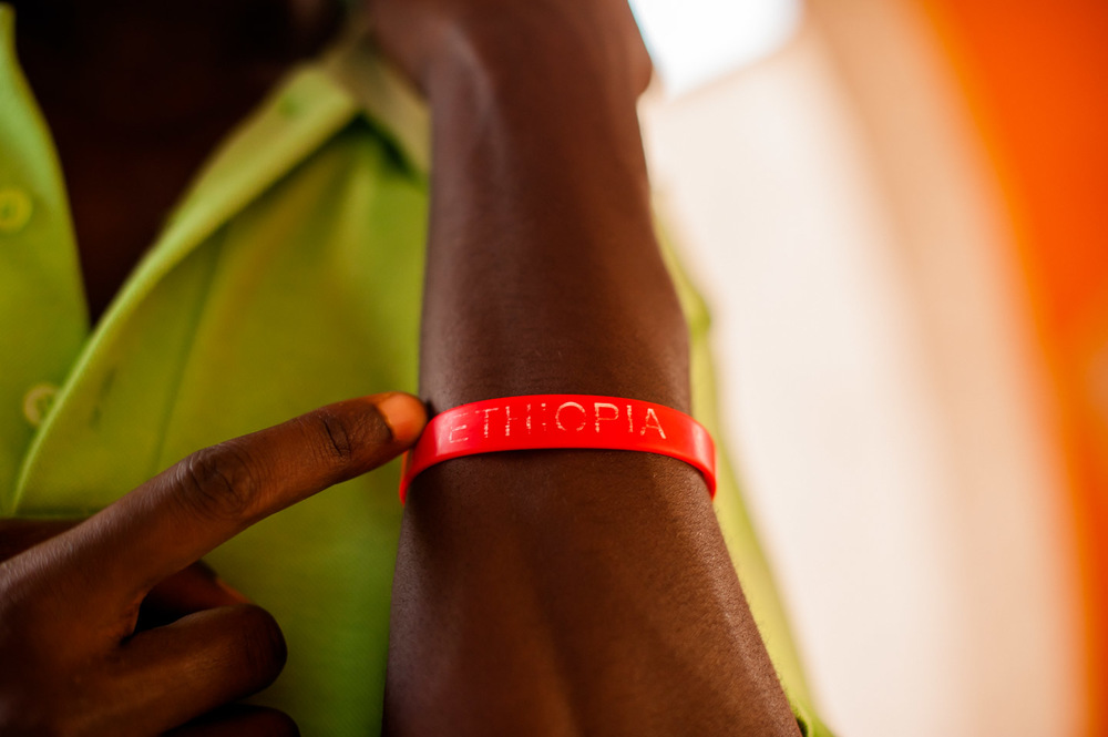"""Yonas, nickname """"Blackberry"""", a server at the café in Habib hotel, proudly shows off his """"Ethiopia"""" wristband. The friendly and warm people of Arba Minch made it so hard to leave. In SNNPR, Ethiopia on February 4, 2014.  Copyright © 2014 Art Zaratsyan"""