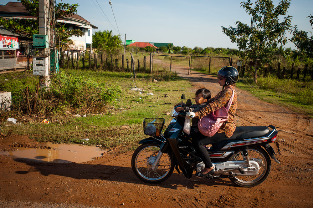 Woman rides a motorcycle with her little boy on a dirt road in Pursat, Cambodia. Motorcycles are the most common means of private transportation in Cambodia. November 20, 2013.  Copyright © 2013 Art Zaratsyan
