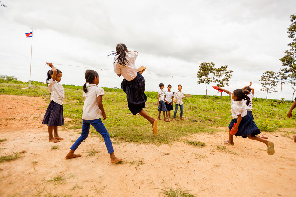 A group of schoolgirls play at recess at a rural elementary school built with the aid of HOPE International Development Agency in Pursat province, Cambodia. The game requires the girls to jump over a rubber band that is stretched out—higher and higher—by the opposite team. The team that can go the highest wins. November 21, 2013.  Copyright © 2013 Art Zaratsyan
