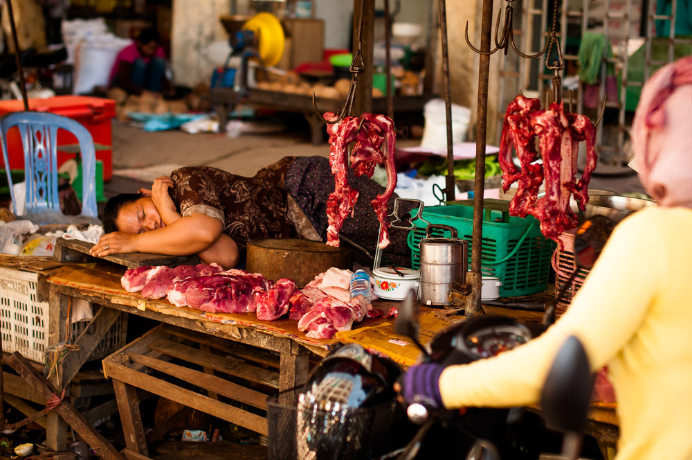 Butcher counter woman is sound asleep in the middle of the busy town market, in Pursat, Cambodia. November 23, 2013.  Copyright © 2013 Art Zaratsyan