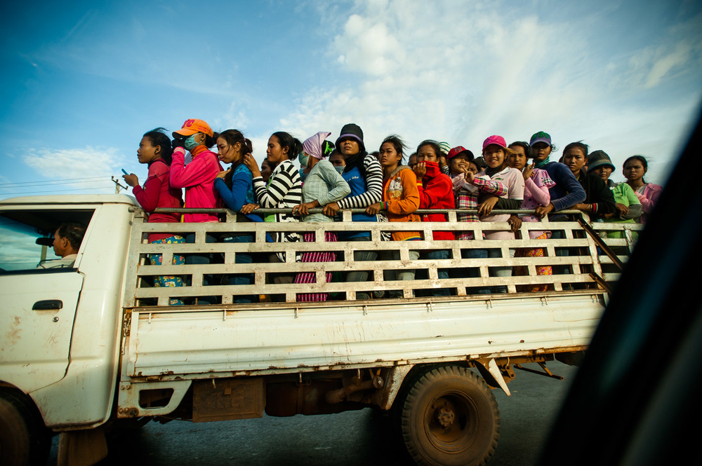Garment factory workers, mostly girls of 16-18 years of age, are heading to work passing by in an endless column of trucks on the road to Phnom Penh. The Cambodian garment factories are infamous for their brutal working conditions and minimal pay. Cambodia. November 27, 2013.  Copyright © 2013 Art Zaratsyan