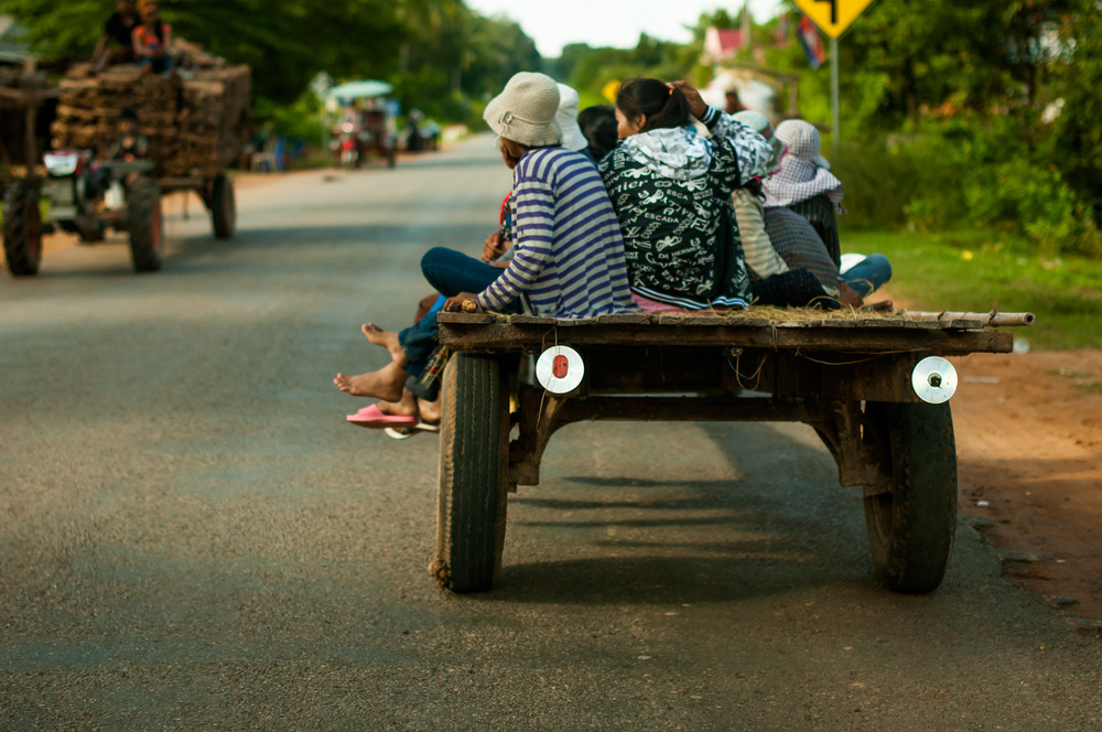 Women return home from the fields. Compact discs are often propped as makeshift reflectors on carts pulled around by mechanical plows in Cambodia, to make them more visible at night. In the province of Pursat, Cambodia, November 22, 2013.  Copyright © 2013 Art Zaratsyan