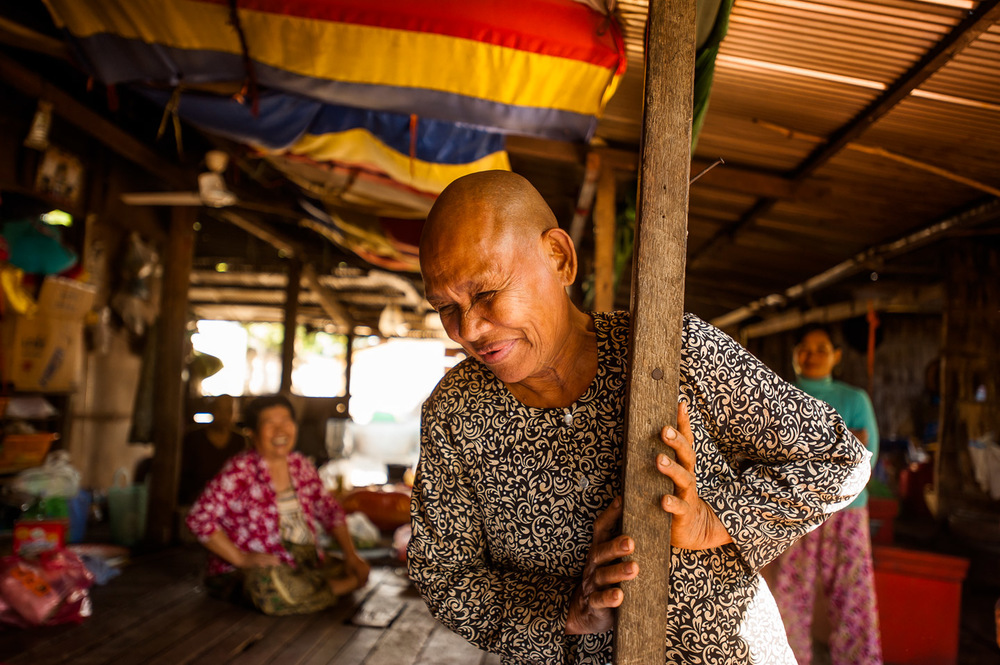 Practically blind, yet full of cheer, this woman is one of many who live in the biggest Buddhist temple of Pursat, Cambodia, having devoted their lives to caring after the monks. November 30, 2013.  Copyright © 2013 Art Zaratsyan