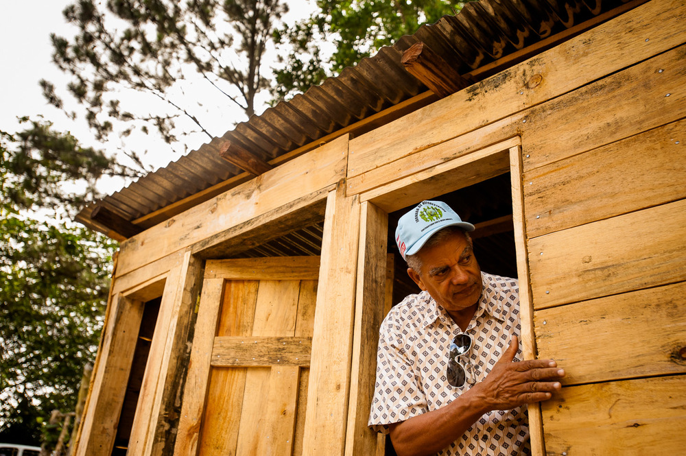 Carlos Bonilla of ADESJO Natural Resources department examines the wood used for the construction of this shed, which will serve as an office at the local sustainable lumber yard in the village of Derrumbado. Bonilla has worked with ADESJO for over 25 years, and is responsible for all the projects involving the natural resources in the province of San José de Ocoa: reforestation, irrigation, soil conservation, to name a few. Under his supervision, he estimates to have planted more than 50,000,000 trees in the area. Dominican Republic, June 30, 2014.  Copyright © 2014 Art Zaratsyan