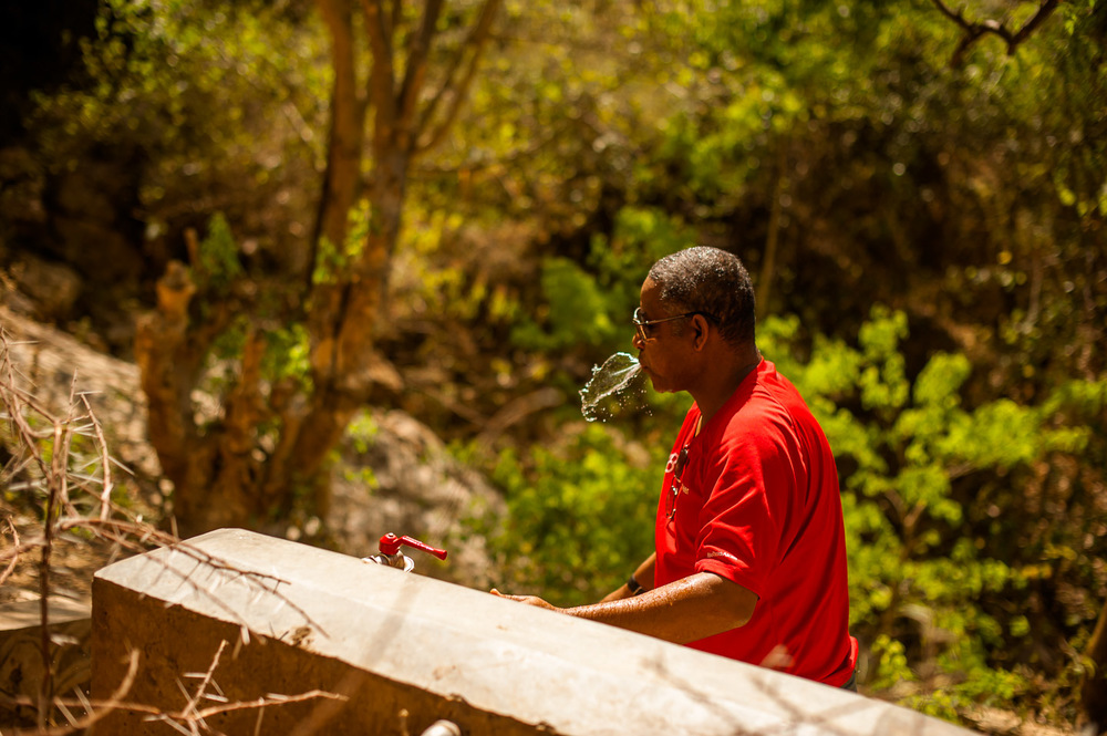 Bereket from the main office of HOPE International Development Agency in Addis Ababa drinks from a water point near the capped source that provides Koshale with clean water. Ethiopia on January 23, 2014.  Copyright © 2014 Art Zaratsyan
