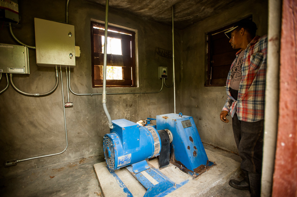 Jorge, head of the men's association of Los Martinez, San José De Ocoa, Dominican Republic, inspects the US-built 11 KW hydro turbine powering the village. July 4, 2014.  Copyright © 2014 Art Zaratsyan