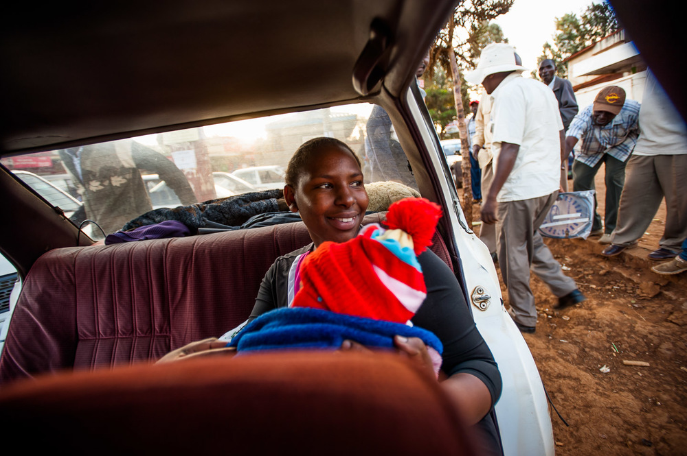 Woman with child, on board a taxi waiting for departure. Usually small sized sedans, the taxis are filled with up to 7 passengers, not counting the driver, before they leave to their destination. In Kianyaga, Kenya, on December 5, 2014. Photo: Art Zaratsyan for Photographers Without Borders