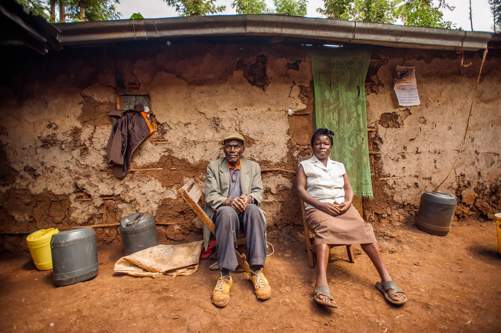 William Njagimbanya, 67, mason, legal aid recipient from Elimu Impact Evaluation Centre in Kiamwaghi village, Kianyaga, Kenya, with his wife in front of their house. William received a parcel of land as part of a dowry, but after the donor's death the land was re-sold by the donor's family to the Anglican Church of Kenya. Elimu is helping William fight against an eviction order and prove his ownership of the land in question. The paperwork for the case is missing, and the case is currently stalled. On December 8, 2014. Photo: Art Zaratsyan for Photographers Without Borders