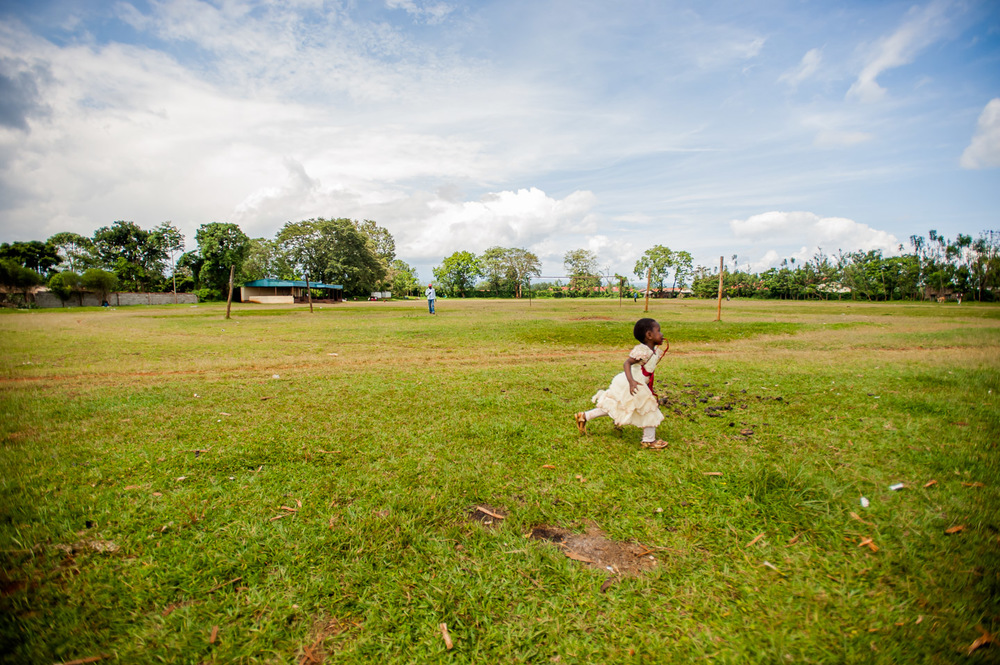 A girl runs across the soccer field in Kianyaga, Kenya, on December 8, 2014. Photo: Art Zaratsyan for Photographers Without Borders
