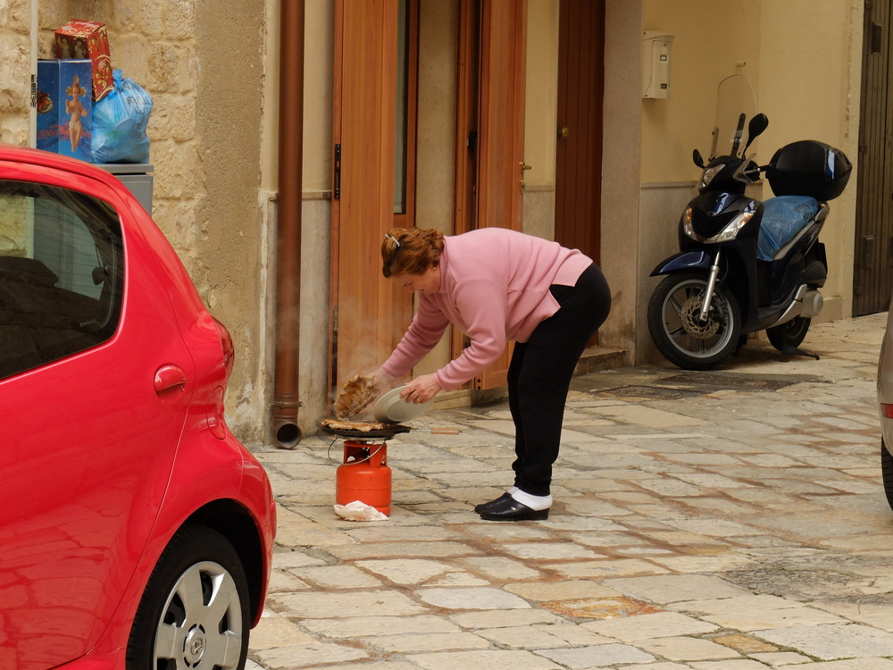 Woman making dinner in the streets outside her home, Bari, Italy