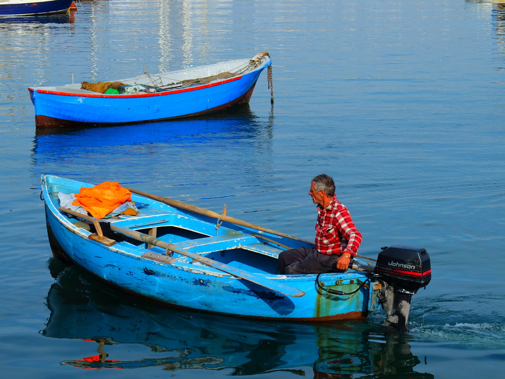 Fisherman on placid waters, Bari, Italy