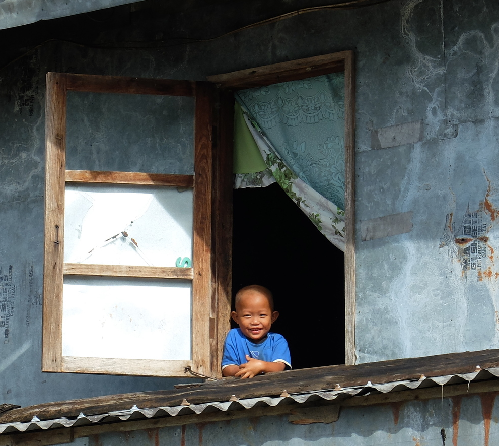 A smiling child waves from the window of his house in Batad, Philippines