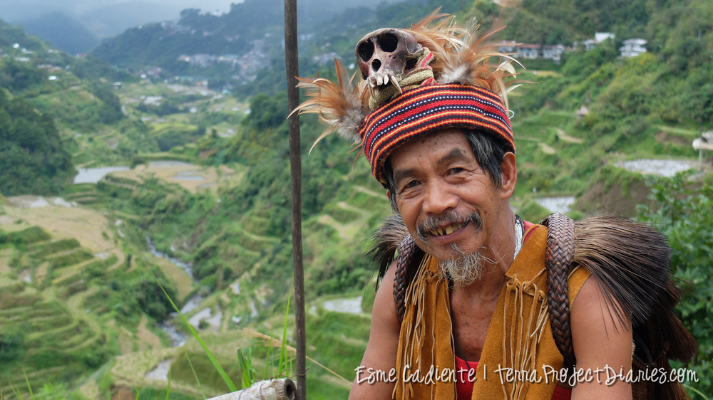 Ifugao Man sitting outside his house in Banaue, Philippines. He made all his clothes including the monkey skull headdress.