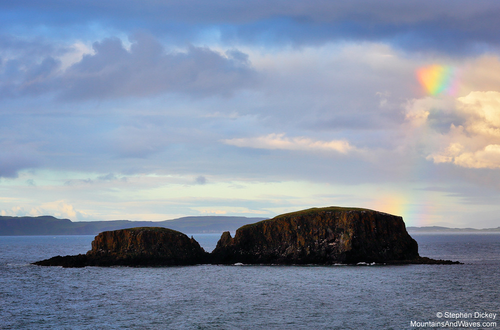 A beautiful rainbow forms over Sheep Island, Ballintoy, as a mixed weather front passes over the coast of Northern Ireland - Northern Ireland landscape photography by Stephen Dickey.
