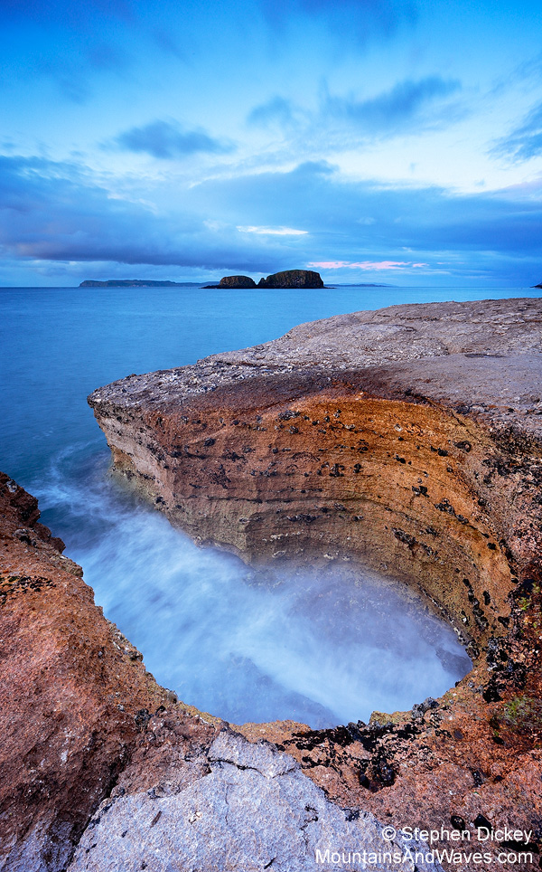 Waves crash into a rock structure known as the 'Keyhole' at Ballintoy - Northern Ireland landscape photography by Stephen Dickey.