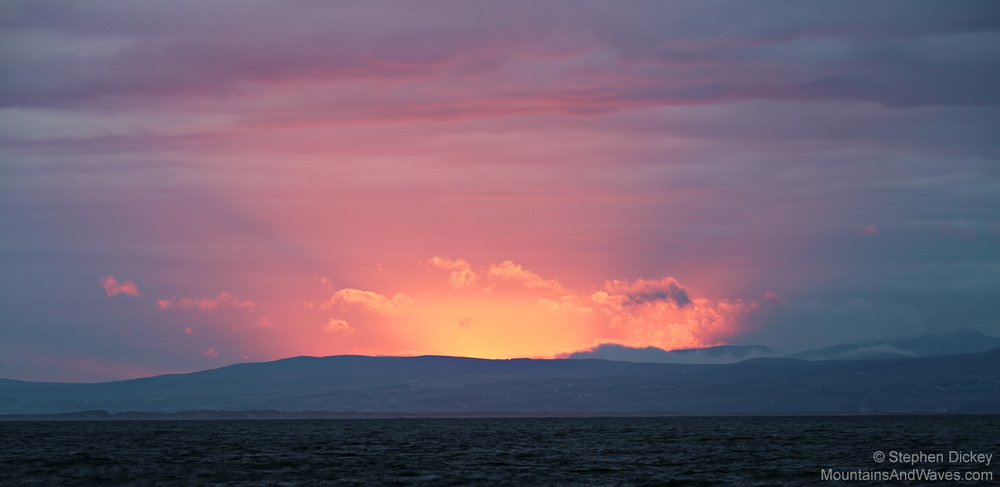 The Sun Bursts Through the Clouds as it Sets Over Donegal, Ireland - Landscape Photography by Stephen Dickey