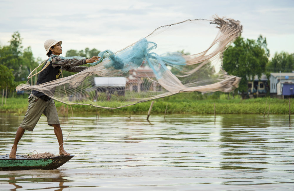 TRAVELIN' LIGHT: A fisherman casts his net expertly from the bow of his boat - Mekong River, Vietnam