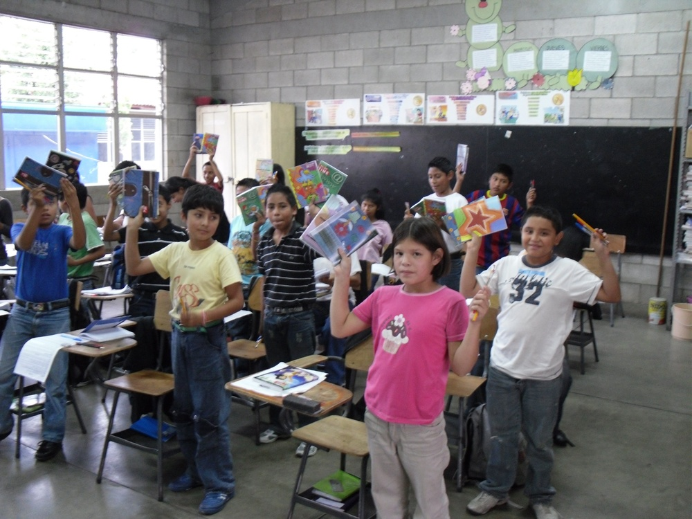 Guatemalan students holding school supplies RWF delivered.