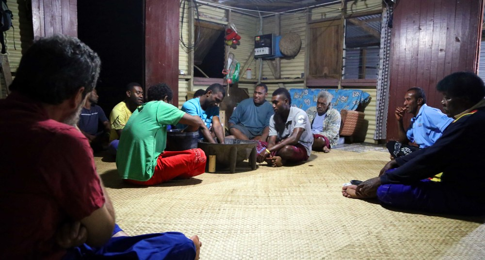 Younger members of the village prepare the kava as the chief sits on the far right.