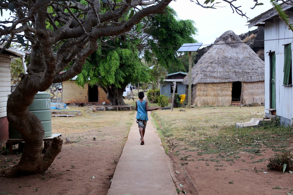 A young boy walks between houses in the Denimanu village on Yadua.