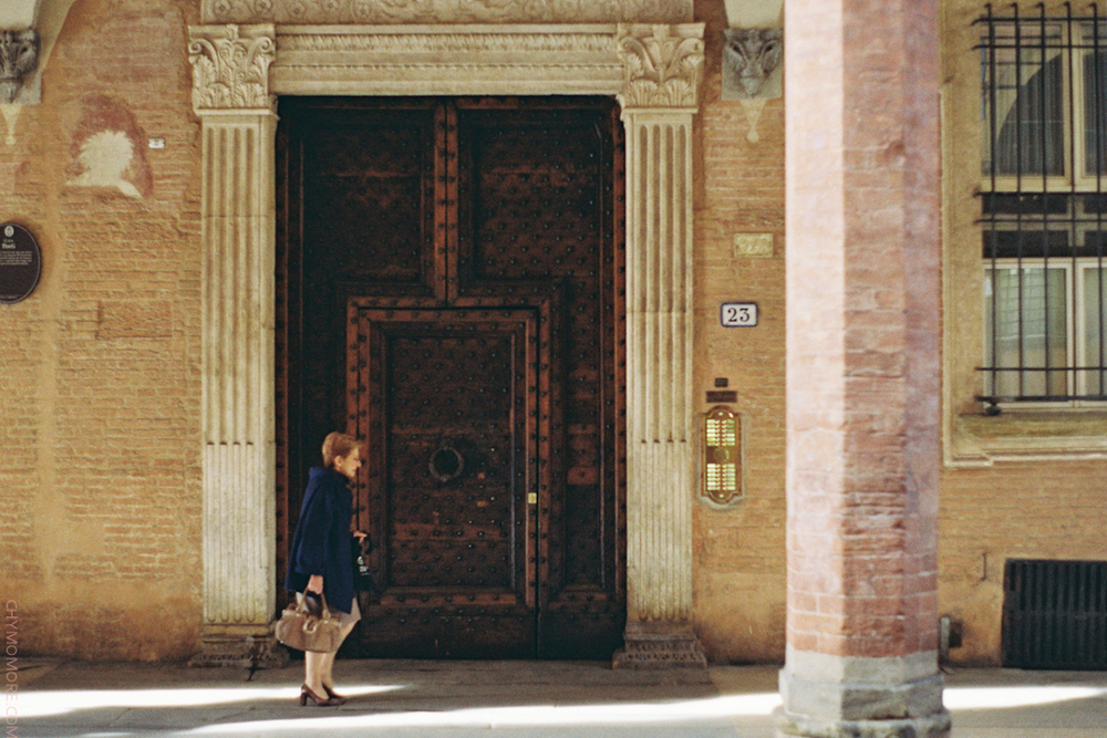 lady walking by the archway of Bologna