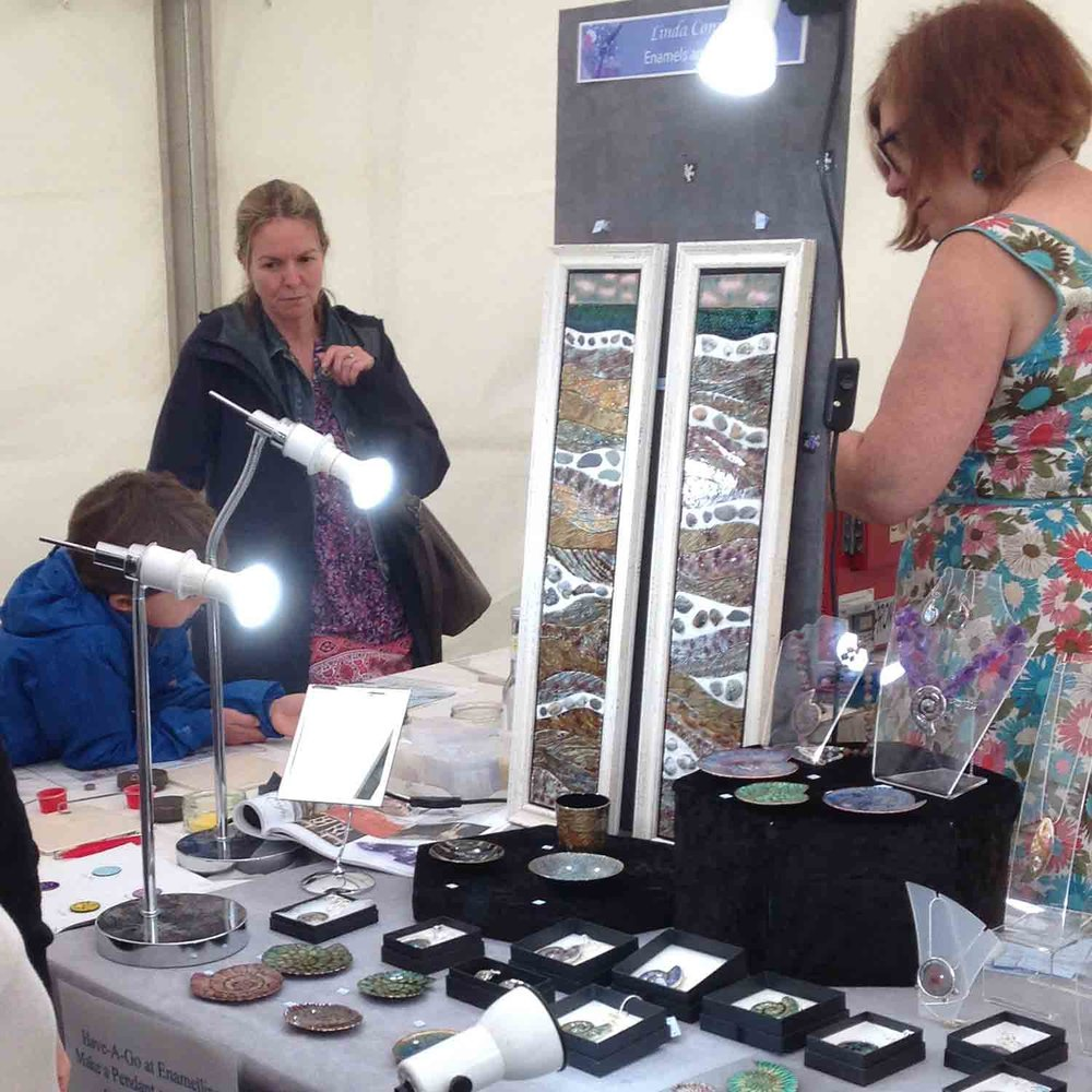 Linda-Connelly-demonstrating-her-enamels-at-an-event.jpg