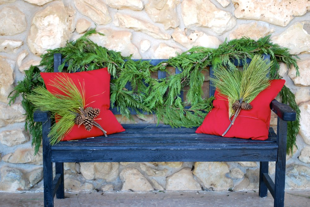 "Holiday Outdoor Styling    Remember the Portlandia ""Put a Bird On It"" episode? Well, grab yourself 25' of fresh evergreen garland and put that stuff everywhere! Drape some fresh garland around your mail box and outdoor bench. Add some red pillows and tie an evergreen sprig and pinecone to them with a pretty ribbon. You can secure the garland and pillows with clear fishing line so it doesn't all blow away in the wind or you can tie a ribbon around it. If you have black lanterns put ornaments or pine cones inside of them and add an evergreen sprig, pine cone and ribbon to the top of each lantern. Speaking of ribbon, we are loving buffalo check ribbon this season. We have used it on our bench pillows, lanterns and wreaths to keep a consistent look. Of course, fresh evergreen wreaths are the perfect welcoming touch for your front door."