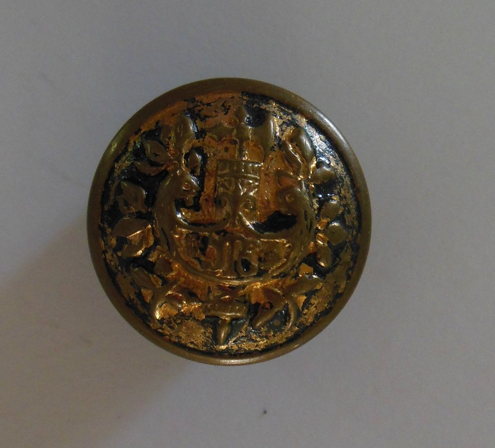This was such a nice button, I put it with the military buttons.  You can see that it once had a black enamel back ground.  It looked to me like a ship with two heads which sent me to the Swedish section of the Big Book of Buttons with no luck.  Once photographed, I can see a fleur- de-lis which might indicate it was French.  Still no luck.  I really think it is also a Suit Coat Button, a nice one at that.