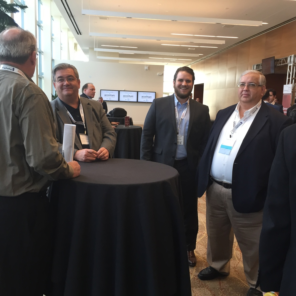 Dennis Gary and Max talk with Kevin Heslin while Joe Maggio takes a picture at the Uptime Institute's Symposium in Santa Clara. Kevin is the Chief Editor of the Uptime Journal.