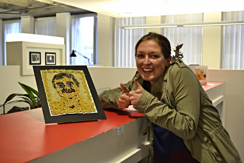 Our receptionist, Nicole Hamlet, gives a big thumbs up for our Human Resources star, Jeanne Karpel'sMacaroni Toniart piece of our CEO Tony Asfour!
