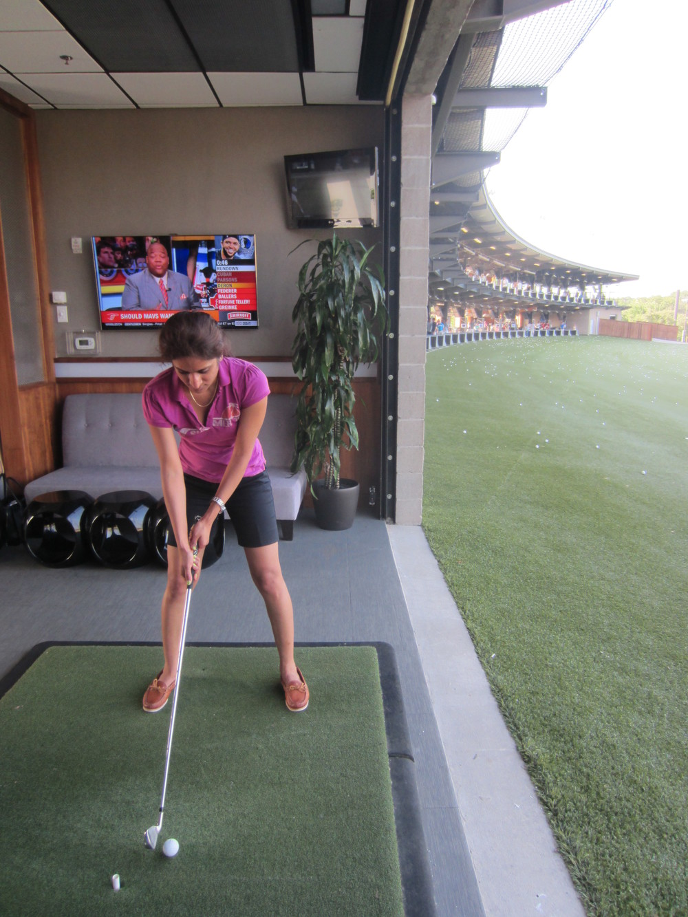 Haritha readies herself for a hole in one at Integrated Design Group's annual summer outing at Top Golf.