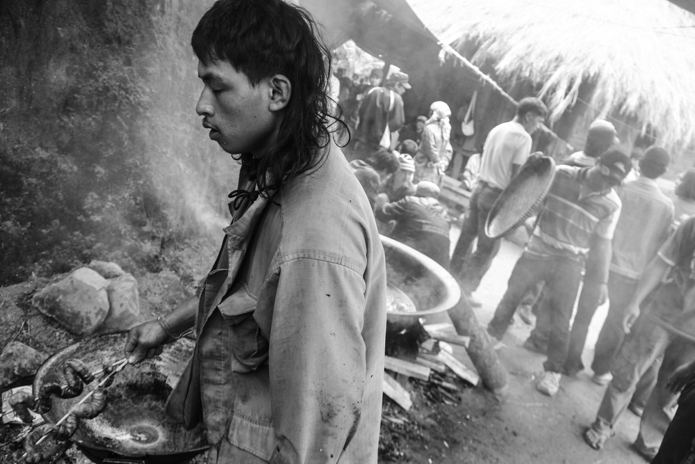 A Ikalahan man holds a pig's intestine. Men are in charge of the butchering and cooking of the meat during feasts. Bushy Village, Kabayan, Benguet.