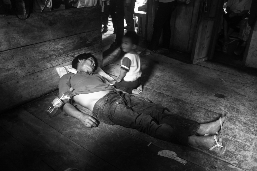 A man lies on the floor after a whole day's celebration of a wedding. Kabayan, Benguet.