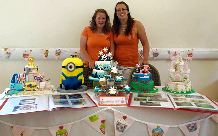 Hannah (right) and Sarah show off their designs at the Cheeki Monkeys children's event