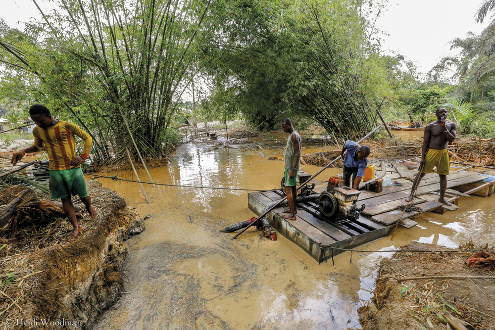 Galamsey operation in Efuanta, Tarkwa.   Many galamsey operations actually take place on the rivers themselves. Miners stand on floating platforms and use a motorised drill and water pump secured on the end of a long pole which is struck into the   riverbed. The contraption has a circular movement of water, pumping  water out as it is driven into the placer deposit and simultaneously sucking water and sand up through a thick pipe. The water and sand from the riverbed are then pumped through a sifting machine lined with a piece of carpet which catches the gold particles (as gold is extremely dense and heavy). The waste water flows back into the river and the process repeats itself; it is not hard to see how quickly a water source can be destroyed.